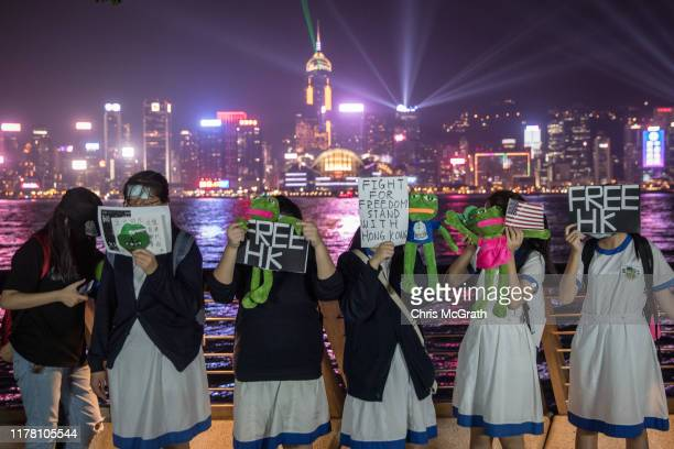 Students hold Pepe toys as they take part in a prodemocracy Pepe the Frog themed human chain protest along the harbor front on September 30 2019 in...