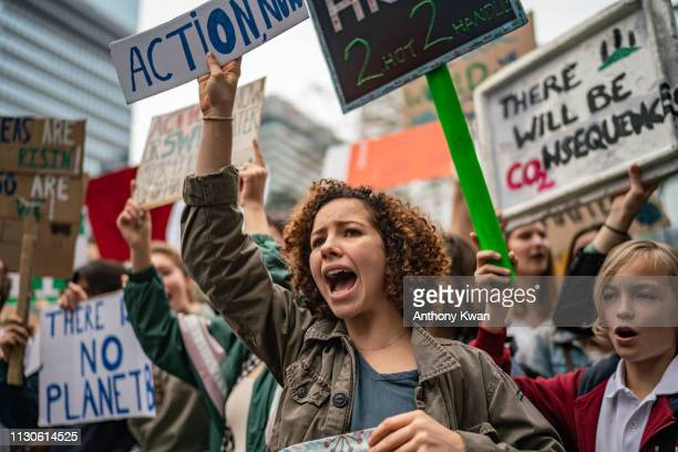 Students hold placards and shout slogans as they participate in a protest on March 15, 2019 in Hong Kong, China. Students around the world took to...