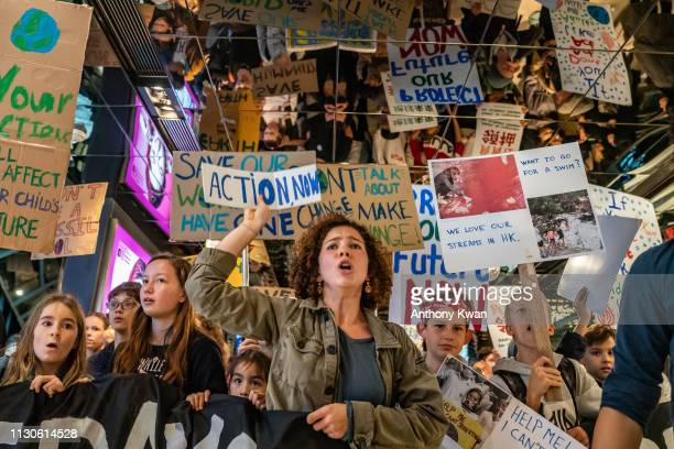 Students hold placards and shout slogans as they participate in a protest on March 15 2019 in Hong Kong China Students around the world took to the...