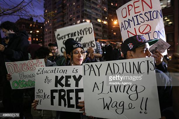 Students hold placards as they stage a demonstration at the Hunter College which is a part of New York City University to protest ballooning student...