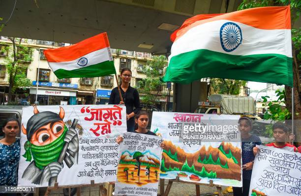 Students hold placards while celebrating the Bharatiya Janata Party for the proposal to remove Article 370 in the state of Jammu and Kashmir in...