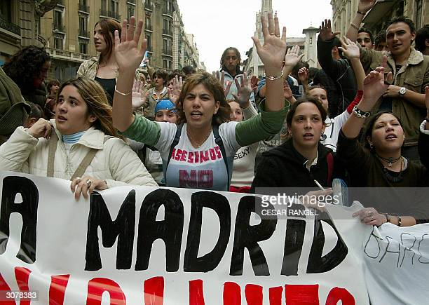 Students hold their hands aloft during a demonstration to protest against acts of terrors and in memory of 198 people killed in the Madrid train...