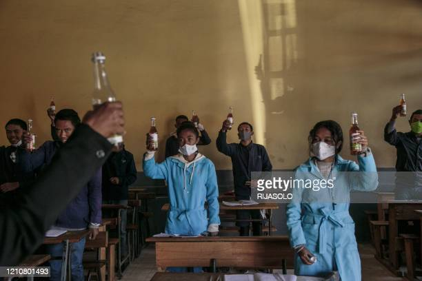 Students hold up a bottles of Covid Organics a herbal tea touted by Madagascar President Andry Rajoelina as a powerful remedy against the COVID19...