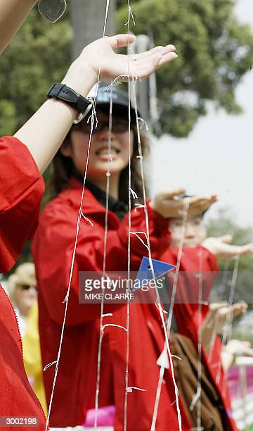 Students hold up pieces of dental floss in a Guinness World Record attempt of making the longest dental floss chain in Hong Kong 22 February 2004 The...