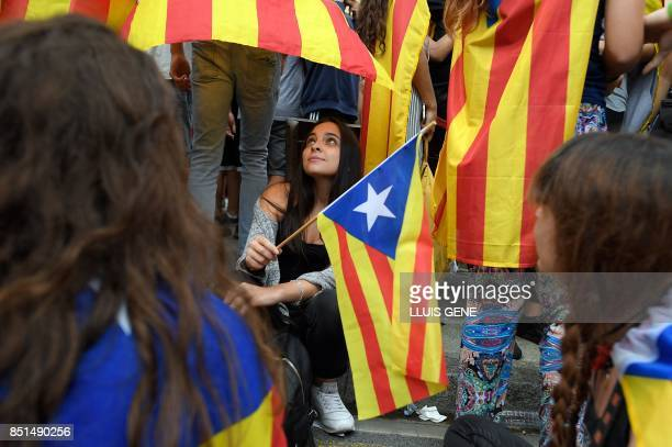 Students holding Catalan proindependence 'esteladas' flags gather in front of the historical headquarters of the University of Barcelona during a...