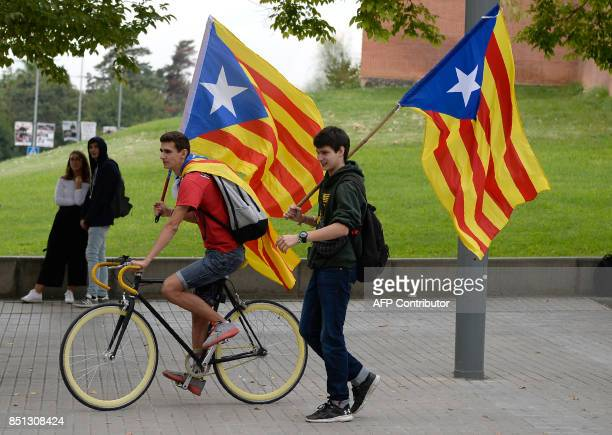 Students holding Catalan proindependence 'esteladas' flags ride a bike during a proreferedum demonstration on September 22 2017 in Barcelona Spain's...