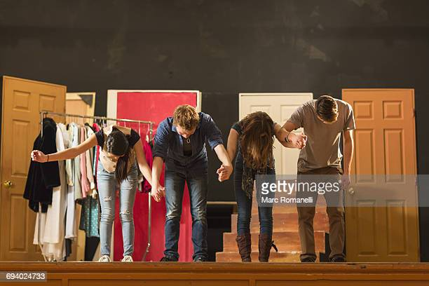 students holding hands on stage and bowing - ator imagens e fotografias de stock