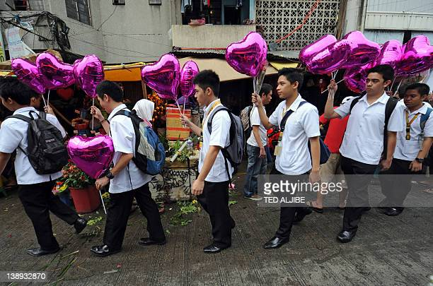 Students holding heartshaped balloons walk past flower stalls on their way to school on Valentine's Day in Manila on February 14 2012 Valentine's Day...