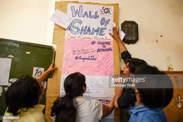 Students holding posters and placards which reads 'Wall of Shame' against the JNU professor Atul Johri at JNU campus on March 21 2018 in New Delhi...