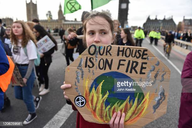 A students holds a placard saying Our world is on fire on Westminster Bridge during the Fridays for Future climate change rally on February 14 2020...