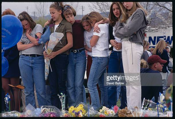Students huddle together in comfort while gathered at a memorial for the victims of the Columbine shooting In May of 1999 students Eric Harris and...