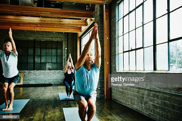 Students in chair pose during class in yoga studio
