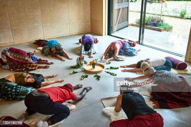 students in child's pose in yoga studio - mid adult men stock pictures, royalty-free photos & images