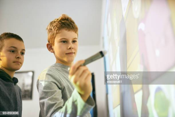 Students in class at interactive whiteboard