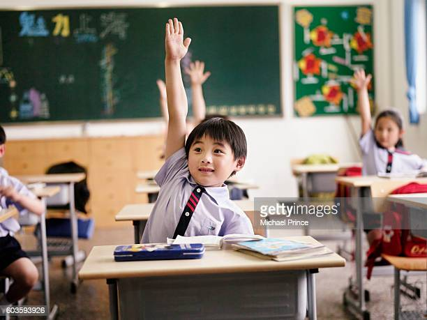 students in classroom raising hands - education stock pictures, royalty-free photos & images