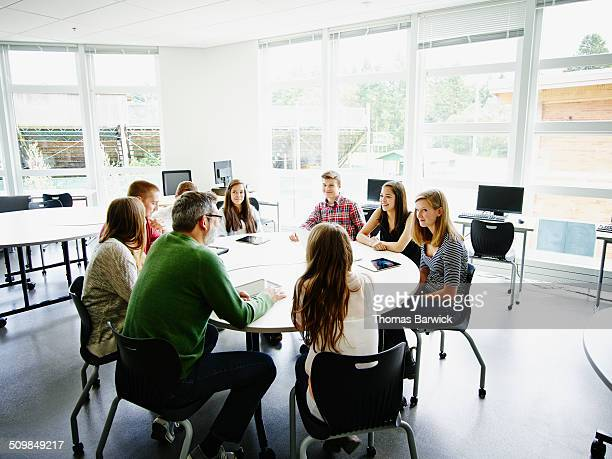 Students in discussion with teacher in classroom
