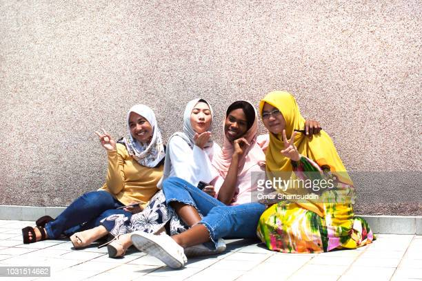 Students in hijab pose for the camera outdoor