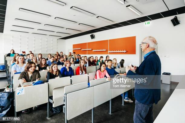 Students In Lecture Theatre Listening To Professor