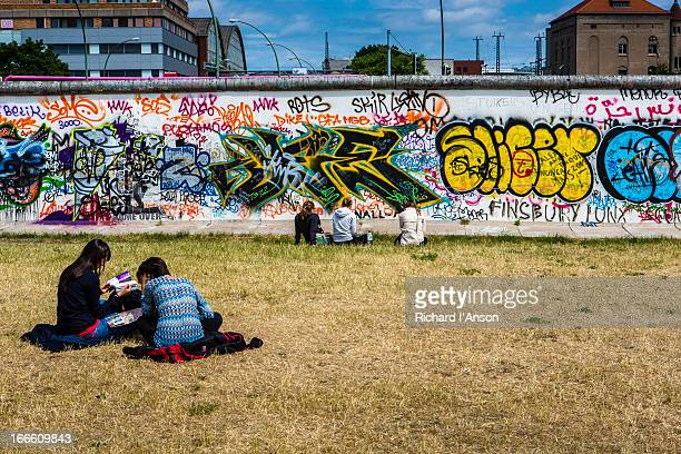 students in park beside remnant of the berlin wall - berlin wall stock pictures, royalty-free photos & images