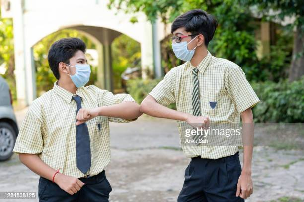 students in the school practicing alternative greeting for safety and protection during covid-19. - reopening stock pictures, royalty-free photos & images