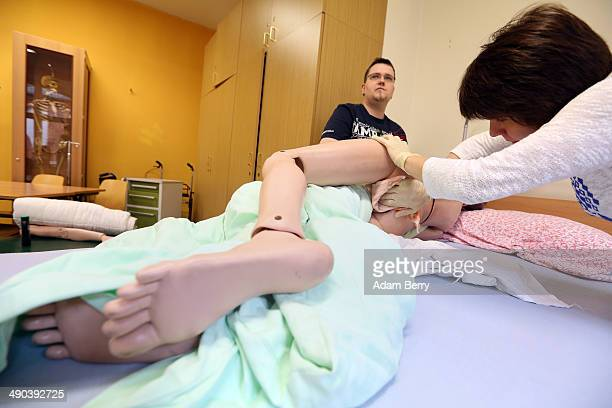 Students Julian Steinberg and Elena Brandt give a bed bath to a mannequin named Frau Schmidt used as a model patient during an elderly care training...