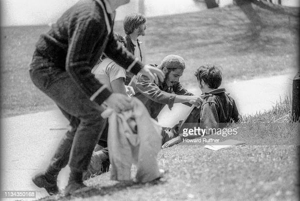 Students kneel on the grass beside wounded classmate John Cleary after the latter had been shot when the Ohio National Guard opened fire on antiwar...