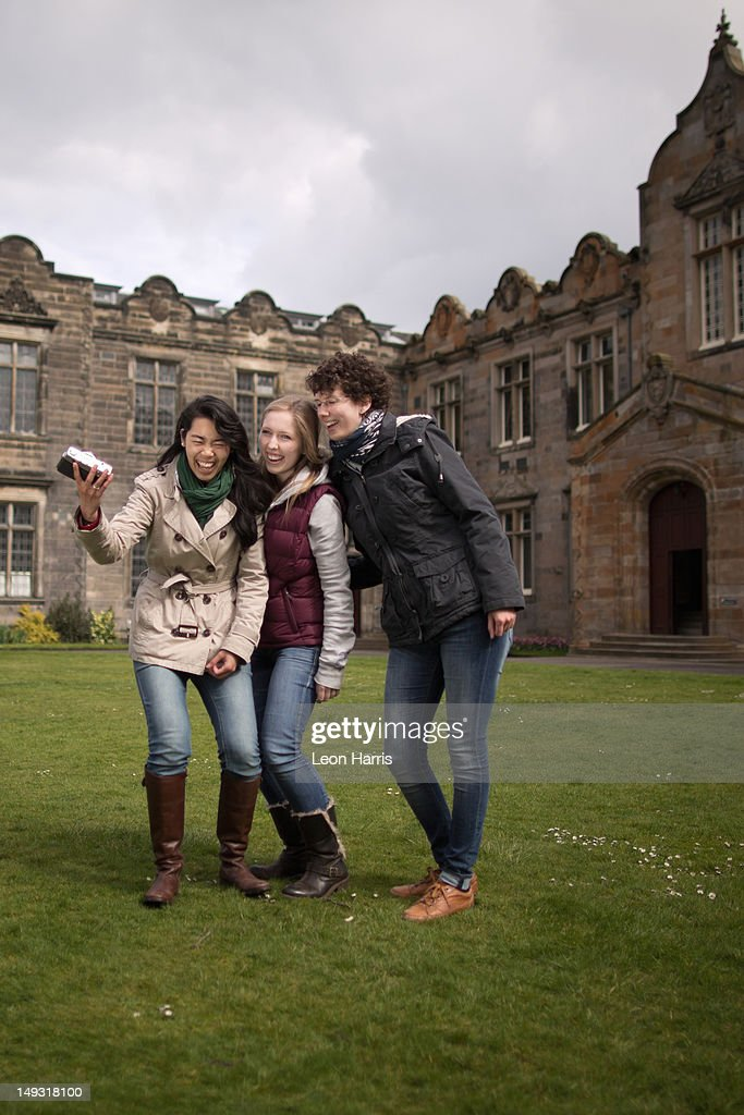 Students laughing together on campus : Stock Photo