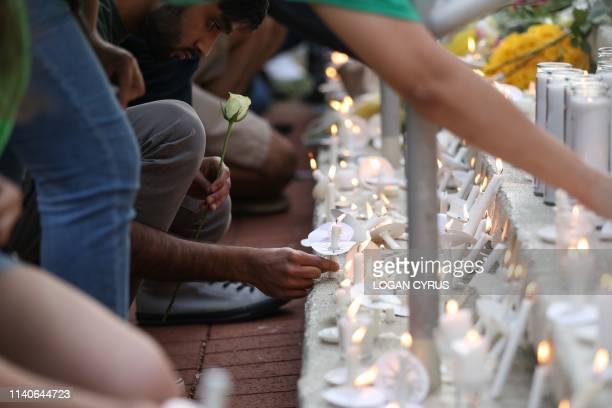 Students lay candles and flowers at the steps of Kennedy Hall to honor the victims of a shooting the day earlier on the University of North Carolina,...