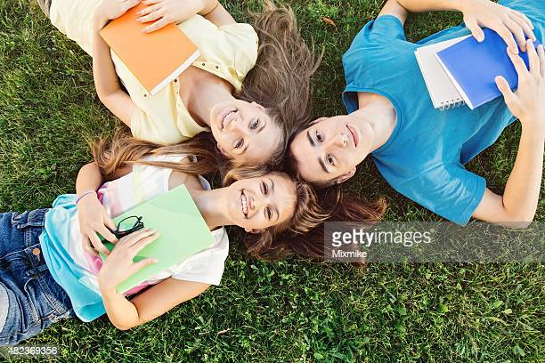 Students laying on a meadow