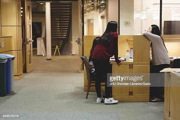 Students lean over a cubicle and chat to take a break from their studies in the Milton S Eisenhower Library on the Homewood campus of the Johns...