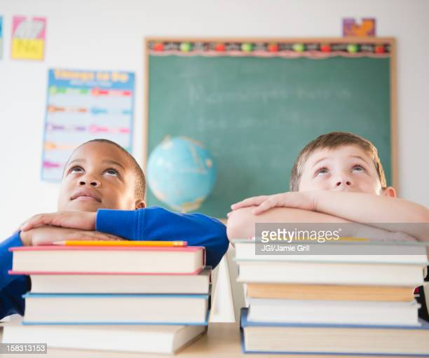 Students leaning on stacks of books in classroom