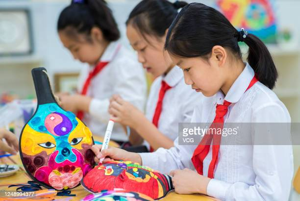 Students learn to draw Mashao facial mask at Hengchangxiang primary school ahead of Cultural and Natural Heritage Day on June 11, 2020 in Hohhot,...