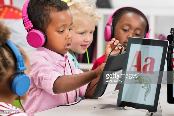 Students learning alphabet with digital tablets
