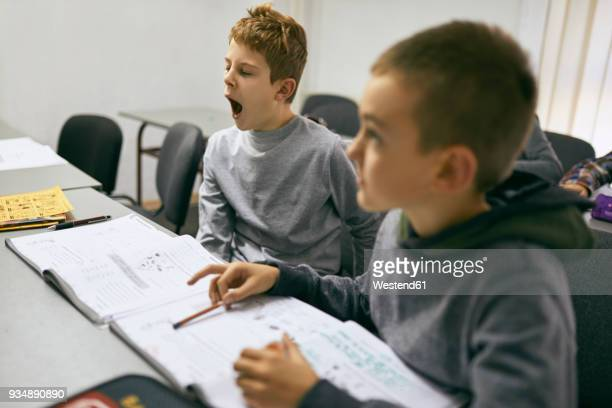 Students learning in class with boy yawning