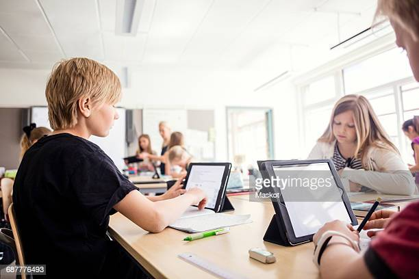 Students learning through digital tablets in classroom