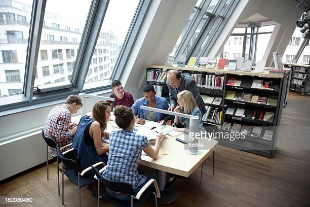 Students learning together with teacher in a library