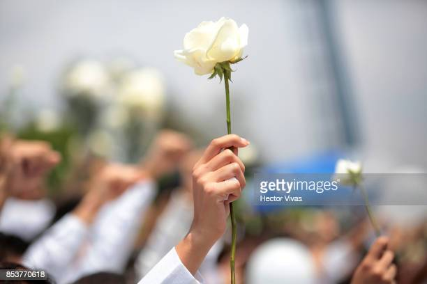 Students lift white flowers in honor of his dead classmates during a ceremony at the Tec de Monterrey Campus Ciudad de Mexico School to pay tribute...