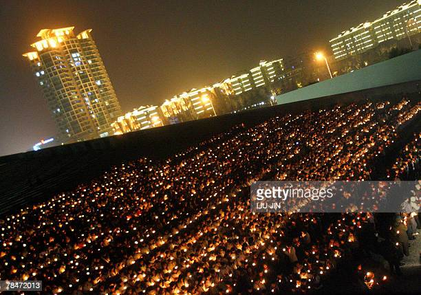 Students light the candles during a memorial event marking the 70th anniversary of Nanjing massacre at the Memorial Hall of the Victims in Nanjing...
