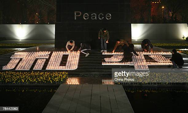 Students light the candles to illuminate Chinese characters reading peace next to a monument during a ceremony to mark the 70th anniversary of...