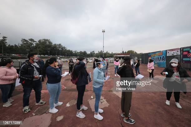 Students line up to allowed their body temperature to be measured prior to enter to take their UNAM admission exam at Olimpico Universitario Stadium...