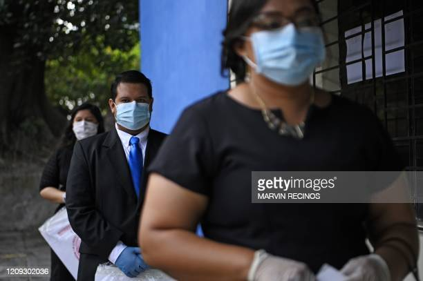 Students line up to receive their diplomas at the University of El Salvador in San Salvador, on April 6, 2020. - 620 students who did not finish...
