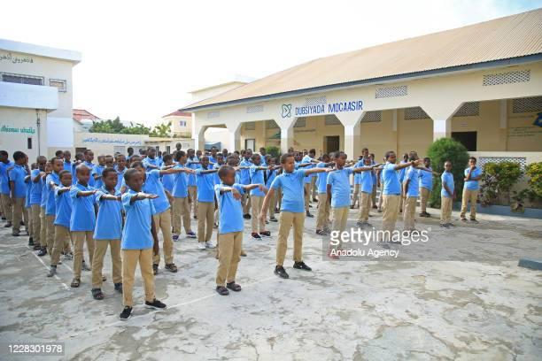 Students lineup in onearm distance in school garden as schools begin in the Somalian capital Mogadishu on September 01 2020 under the measures taken...