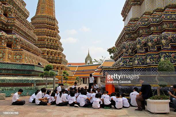Students listen to stories provided by the local buddhist monk at the Wat Phra Kaew. Temple of the Emerald Buddha is regarded as the most sacred...