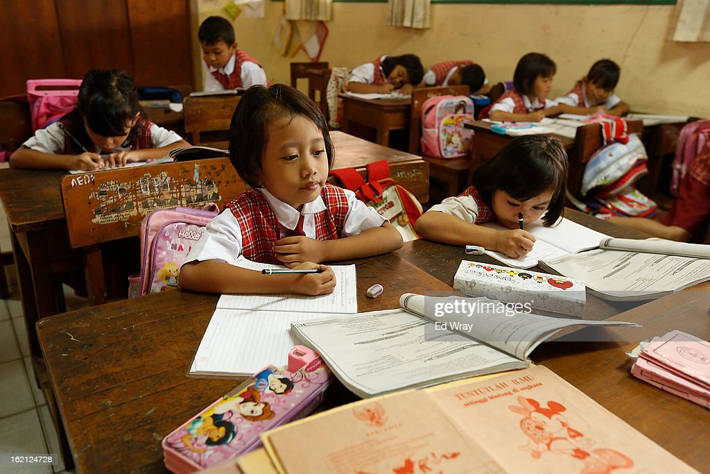 Students listen to their teacher during a 3rd grade social studies class on February 19, 2013 in Jakarta, Indonesia. A new schools curriculum to take effect in July, 2013 has drawn criticism for its plans to drop science and english classes to provide more time for social and religious education, at a time when Indonesian students are falling behind other countries in the region in Science and Math.