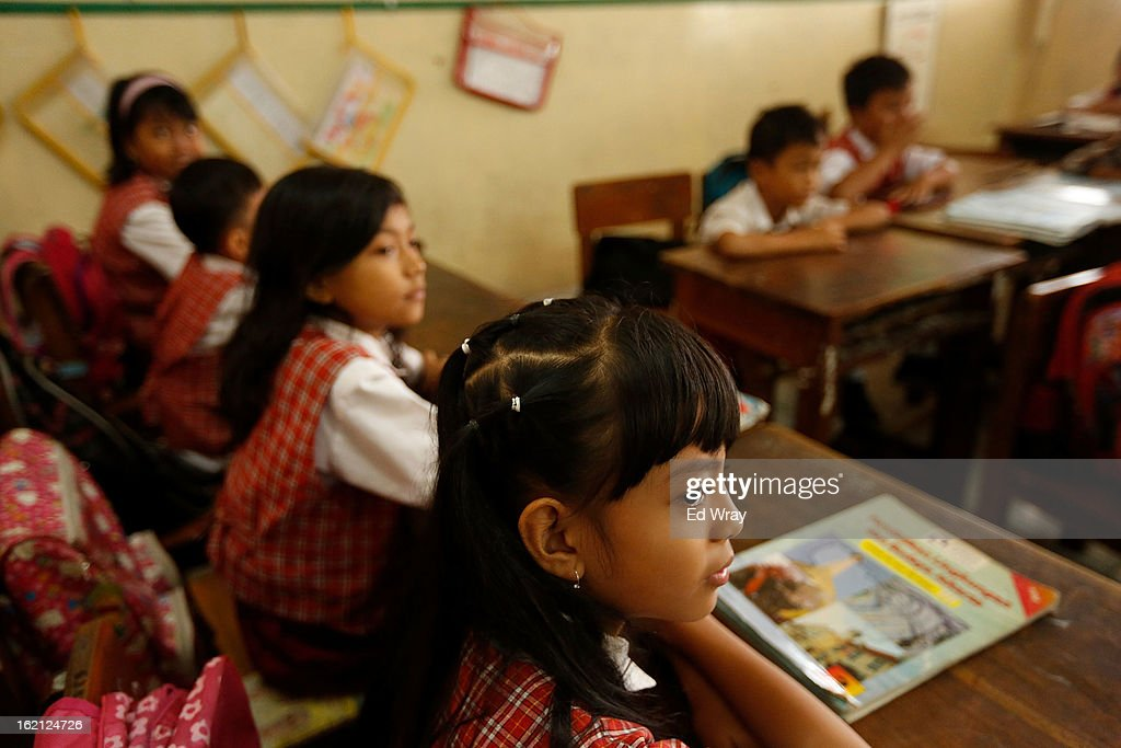 Students listen to their teacher during a 4th grade social studies class on February 19, 2013 in Jakarta, Indonesia. A new schools curriculum to take effect in July, 2013 has drawn criticism for its plans to drop science and english classes to provide more time for social and religious education, at a time when Indonesian students are falling behind other countries in the region in Science and Math.