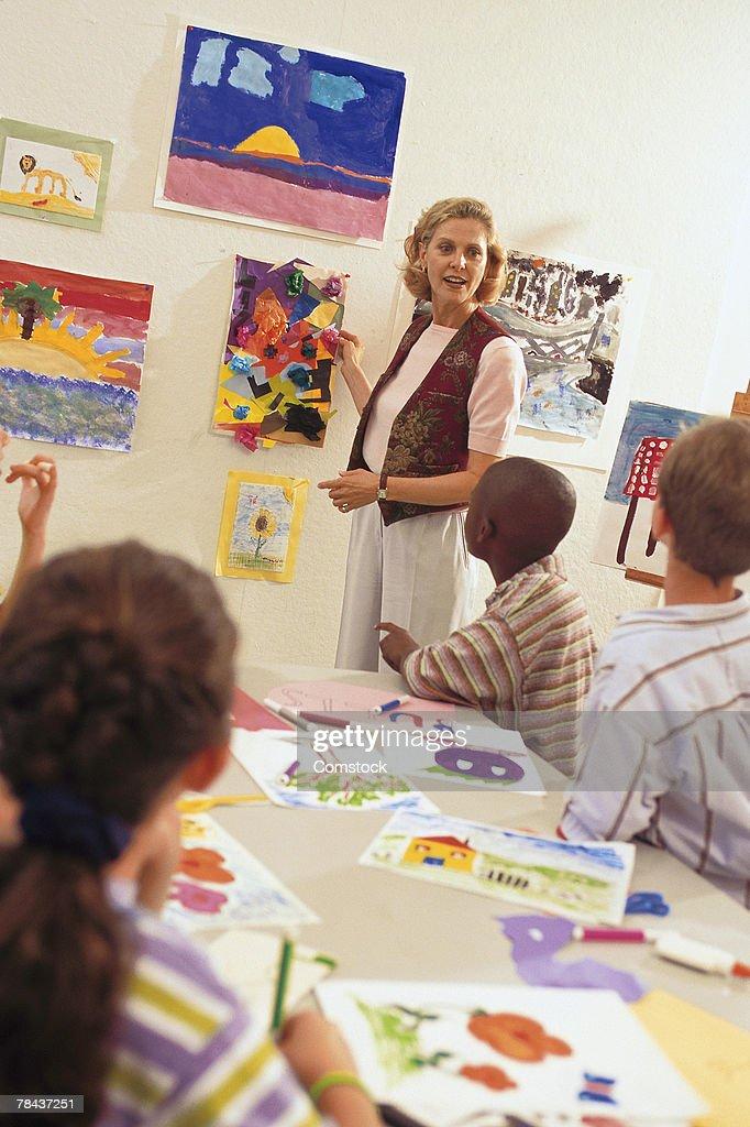 Students listening to art teacher in classroom : Stockfoto