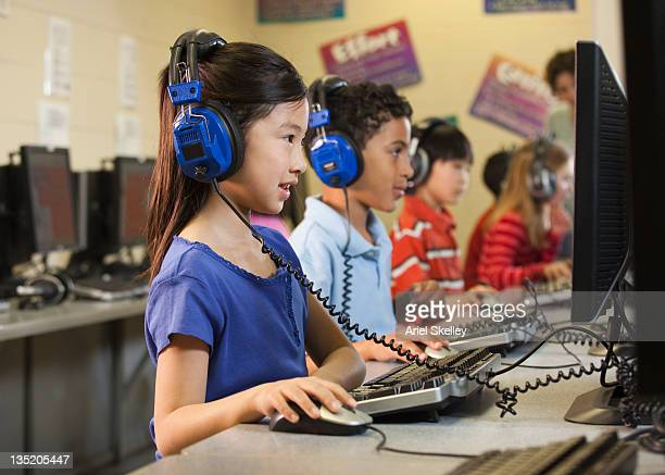 Students listening to headphones at computers in classroom