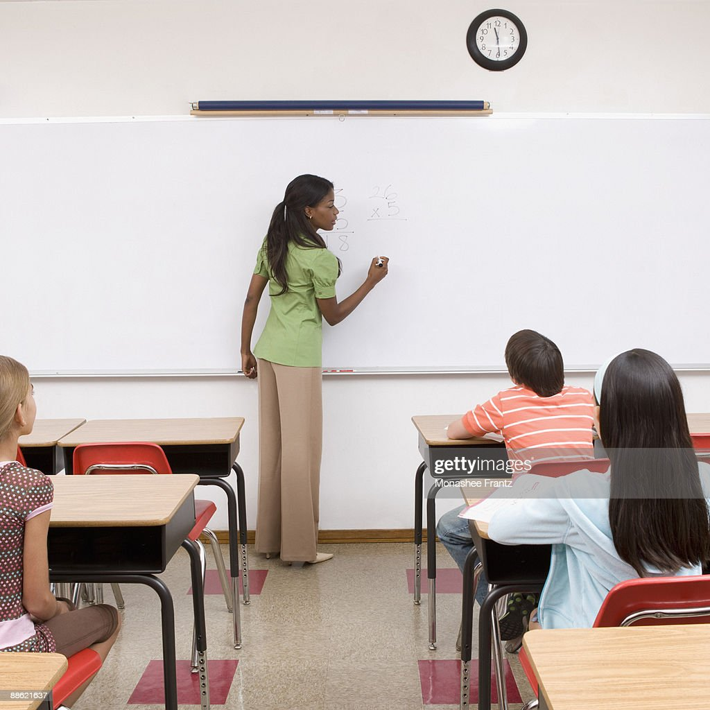 Students listening to teacher in classroom : Stock Photo