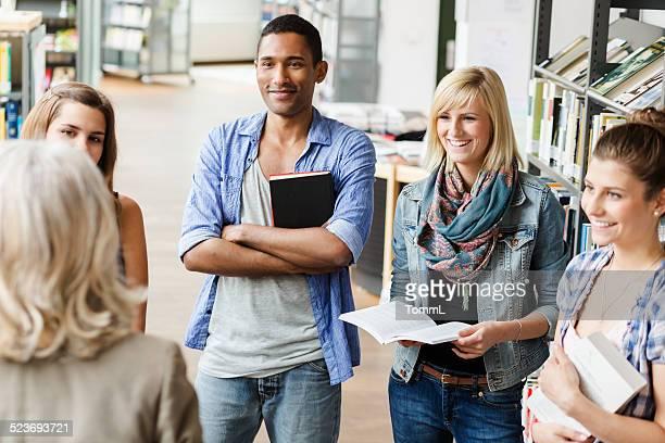Studenten In der Bibliothek hören Lehrer