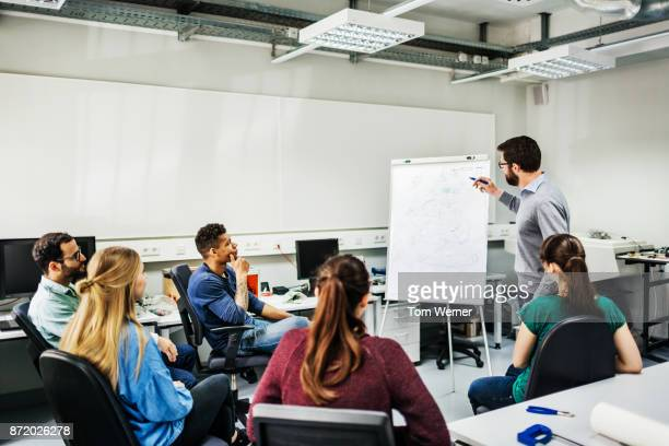students listening to tutor during seminar at university - academy stock pictures, royalty-free photos & images